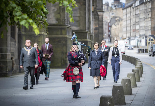 """Piper Louise Marshall plays the pipers' march """"Heroes of St Valery"""" and leads the procession down Edinburgh's Royal Mile. (PA Images)"""
