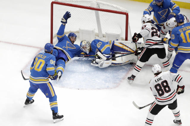 Chicago Blackhawks' Adam Boqvist, right, of Sweden, is unable to score as St. Louis Blues goaltender Jordan Binnington (50), Robert Bortuzzo and Ryan O'Reilly (90) defend during the second period of an NHL hockey game Saturday, Dec. 14, 2019, in St. Louis. (AP Photo/Jeff Roberson)