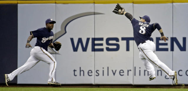 Milwaukee Brewers' Elian Herrera watches as teammate Ryan Braun (8) makes a running catch on a ball hit by Pittsburgh Pirates' Jordy Mercer during the seventh inning of a baseball game Wednesday, May 14, 2014, in Milwaukee. (AP Photo/Morry Gash)