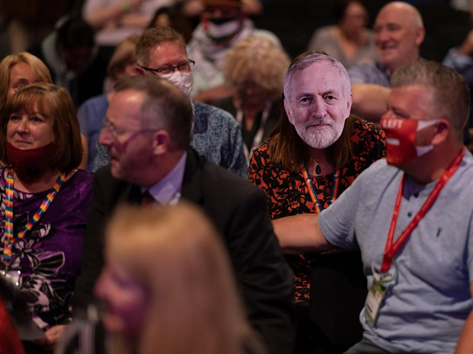A delegate wears a Corbyn mask in the main hall on day one of the Labour Party conference (Getty)