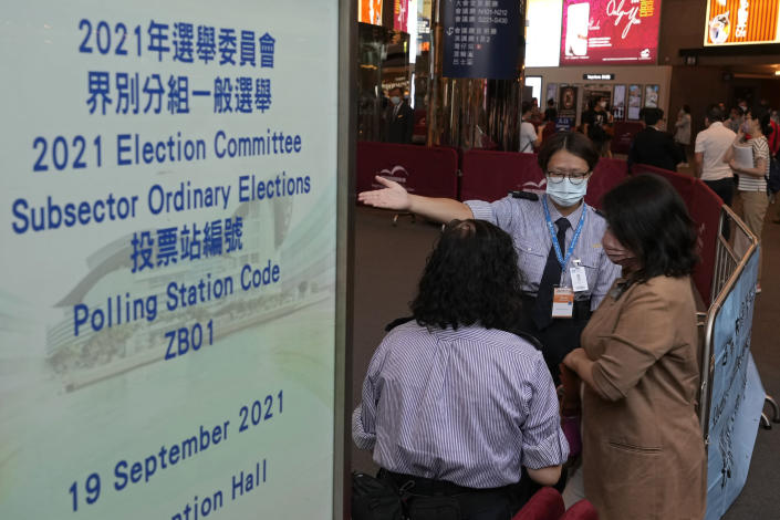 """Voters enter a polling center for the election committee that will vote for the city's leader in Hong Kong Sunday, Sept. 19, 2021. Hong Kong's polls for an election committee that will vote for the city's leader kicked off Sunday amid heavy police presence, with chief executive Carrie Lam saying that it is """"very meaningful"""" as it is the first election to take place following electoral reforms. (AP Photo/Vincent Yu)"""