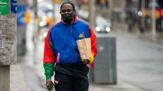 A pedestrian in a mask and spring jacket walks through downtown Ottawa during the COVID-19 pandemic. (Andrew Lee/CBC - image credit)