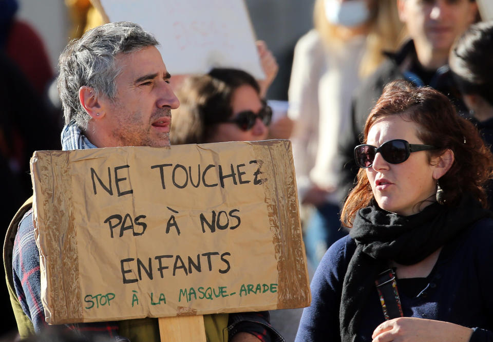 """A man holds a placard reads """"Don't touch our children"""" as he demonstrates in Bayonne, southwestern France, against wearing masks at school, Sunday, Nov. 29, 2020. In France, wearing a mask at school is compulsory from 6 years old. (AP Photo/Bob Edme)"""