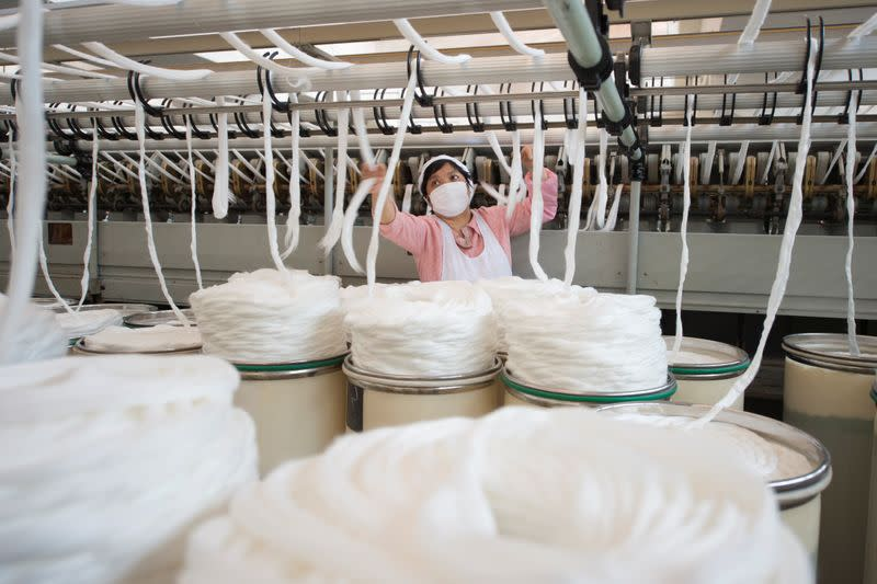Employee wearing a face mask works on the production line at a textile factory in Haian