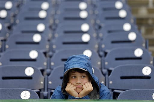 Bennett Cheer, 12, Williston, Vt., sits in the rain before a baseball game between the Washington Nationals and the New York Mets at Nationals Park Thursday, June 6, 2013, in Washington. (AP Photo/Alex Brandon)
