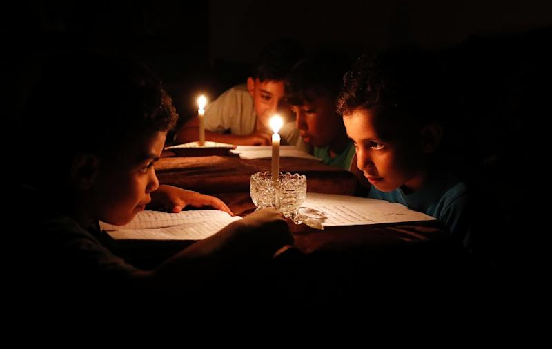 (FILES) This file photo taken on June 13, 2017 shows Palestinian children at home reading books by candle light due to electricity shortages in Gaza City (AFP Photo/THOMAS COEX)