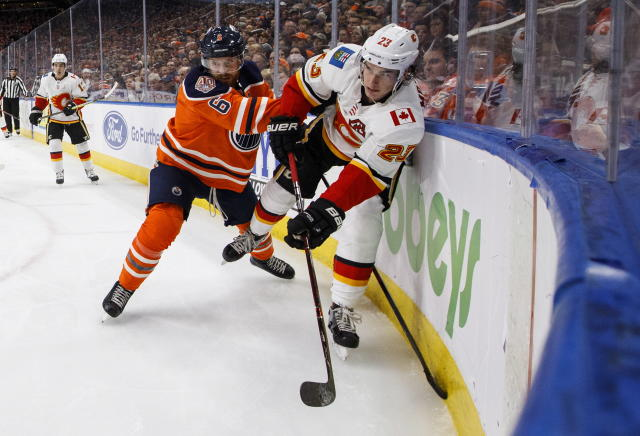 Calgary Flames' Sean Monahan (23) is checked by Edmonton Oilers' Adam Larsson (6) during the third period of an NHL hockey game in Edmonton, Alberta, Saturday, Jan. 19, 2019. (Jason Franson/The Canadian Press via AP)