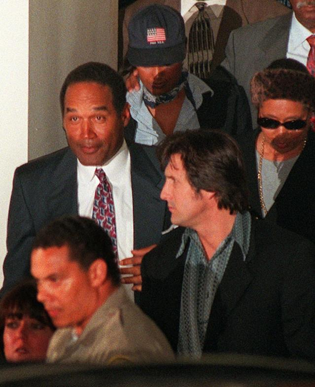 <p>O.J. Simpson, left, leaves Los Angeles County Superior Court in Santa Monica, Calif., after the verdict in the wrongful death civil suit against him Tuesday, Feb. 4, 1997. Simpson was found liable on all counts. (Photo: Michael Caulfield/AP) </p>