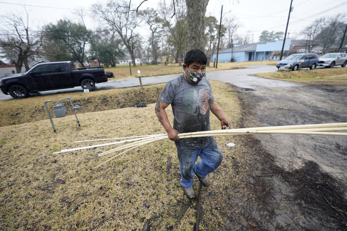 West Street Recovery's Martin Uribe works to repair busted pipes at a home, were the pipes froze during a recent winter storm, Thursday, Feb. 25, 2021, in Houston. West Street Recovery, a nonprofit created in the wake of Hurricane Harvey to help repair flood damaged homes, has been working since the winter storm hit to repair and replace damaged plumbing systems for residents who can't afford to do so. (AP Photo/David J. Phillip)