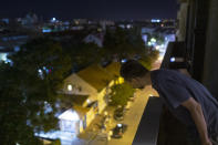 In this photo taken on Friday, July 2, 2021, Nemanja Dragic, 36, looks at a bar across the street from his balcony in Belgrade, Serbia. Serbia's capital is vibrating with nightlife again after over a year of pandemic restrictions. Cafes, bars and fun-hungry customers are celebrating a summer boom in business and entertainment options. But the accompanying loud music and noise are a bust for residents across Belgrade. (AP Photo/Marko Drobnjakovic)
