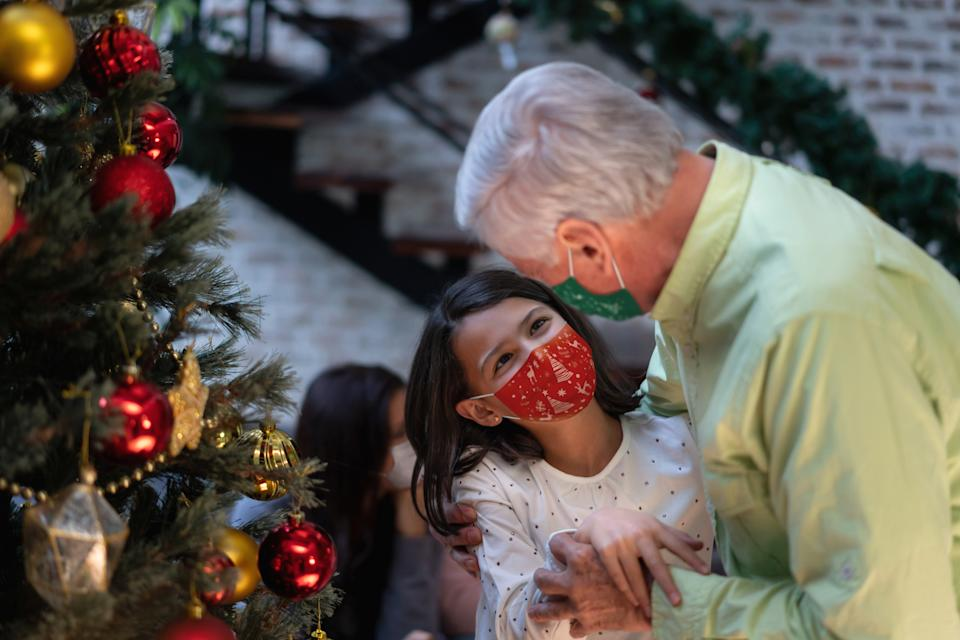 Portrait of a loving girl with her grandfather wearing facemasks while celebrating Christmas at home during the COVID-19 pandemic