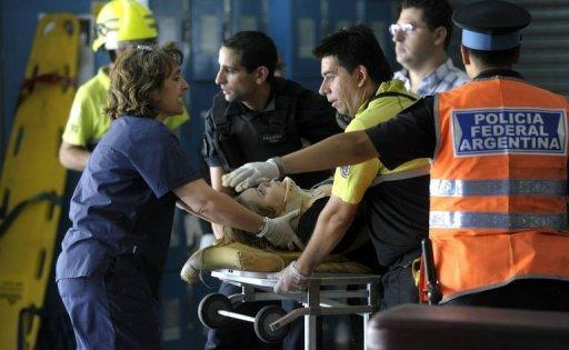 Police and rescue workers transport an injured woman on a stretcher after a train crashed at Once train station in Buenos Aires