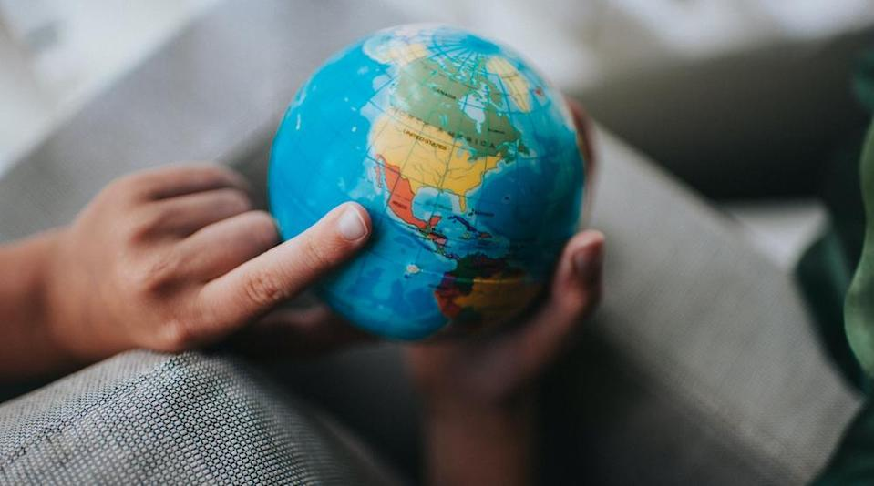 Conceptual images of a globe. Child pointing to Mexico.