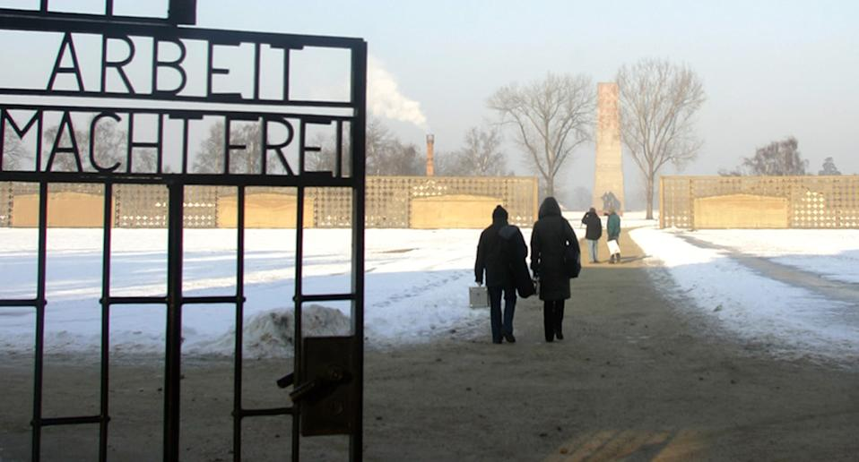 People pass the entrance of the former Nazi concentration camp Sachsenhausen.