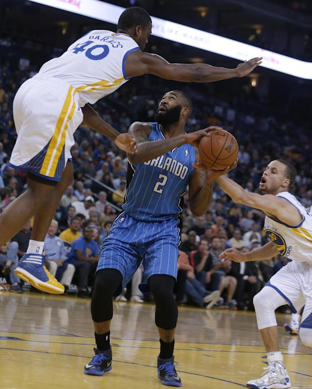 Orlando Magic forward Kyle O'Quinn, center, attempts a shot between Golden State Warriors' Harrison Barnes, left, and Stephen Curry during the first half of an NBA basketball game Tuesday, March 18, 2014, in Oakland, Calif. (AP Photo/Ben Margot)