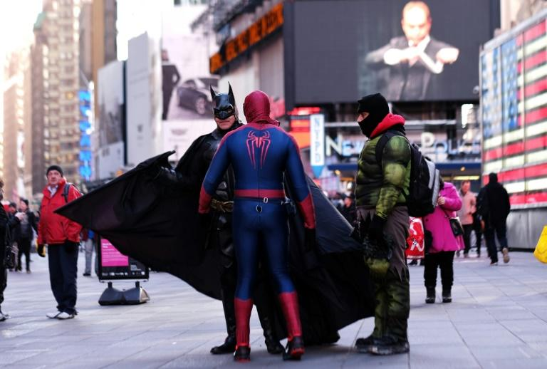 Spider Man, The Hulk and Batman confer at Times Square in New York on February 27, 2015 -- they are among dozens of men and women who earn their livelihood dressing up as cartoon characters and super heroes to pose with tourists for tips (AFP Photo/JEWEL SAMAD)