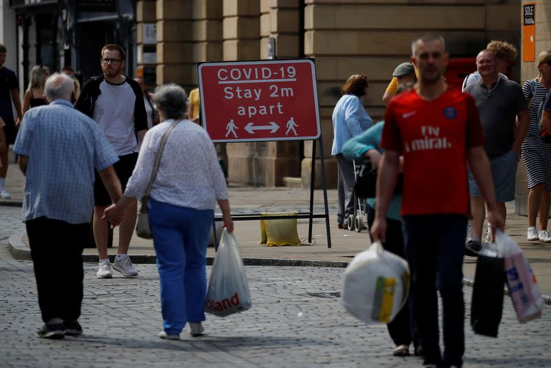 FILE PHOTO: Shoppers walk past a social distancing sign following the outbreak of the coronavirus disease (COVID-19) in Chester, Britain