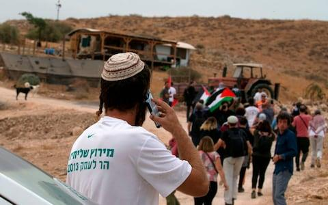 An Israeli settler speaks on the phone while Palestinian protesters and foreign activists enter a settlement outpost during a demonstration - Credit: JAAFAR ASHTIYEH/AFP via Getty Images