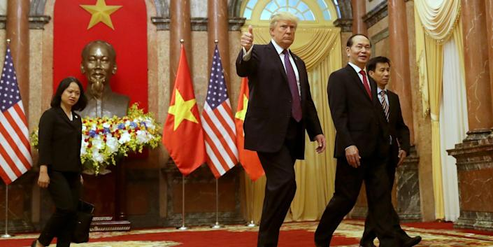 President Donald Trump, center, and Vietnamese President Tran Dai Quang, center right, arrive for the bilateral meeting at the Presidential Palace, Sunday, Nov. 12, 2017, in Hanoi, Vietnam.