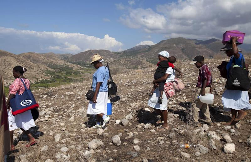 "In this Feb. 9, 2014 photo, Christian pilgrims return home after attending a Catholic gathering in the village of Bois-Neuf, Haiti. At the gathering entitled ""Prayer, Penance and Conversion,"" people came with hopes of a better life for themselves or others. (AP Photo/Dieu Nalio Chery)"