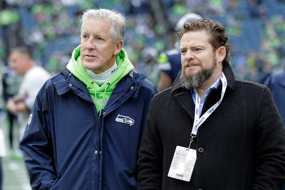 In this Dec. 30, 2018, file photo, Seattle Seahawks coach Pete Carroll, left, talks with general manager John Schneider before  the team's NFL football game against the Arizona Cardinals in Seattle. There is a clear and obvious need for the Seahawks to address along the defensive line and it happens to be one of the deeper positions of talent in the entire draft. That may be far too simplistic and straightforward for Schneider and Carroll. Schneider is always good for a few surprises in the draft, and more than a couple of trades.