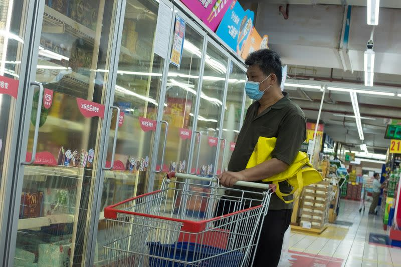 A man looks at frozen food products in a supermarket in Beijing