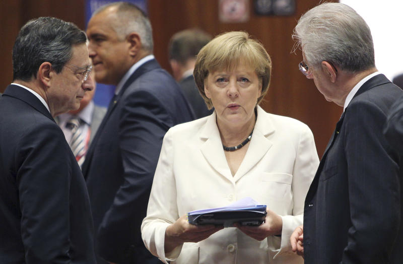 FILE - In this June 29, 2012 file photo, German Chancellor Angela Merkel, center, speaks with European Central Bank President Mario Draghi, left, and Italian Prime Minister Mario Monti during a round table meeting at a EU Summit in Brussels. The worst of Europe's financial crisis appears to be over. European leaders have taken steps to ease the panic that has plagued the region for three turbulent years. Much of the credit for easing Europe's financial crisis goes to the European Central Bank, which has become more aggressive over the past year under the leadership of Mario Draghi. Merkel has also helped ease financial tensions across the region by speaking more forcefully about the need to hold the euro together. (AP Photo/Michel Euler, File)