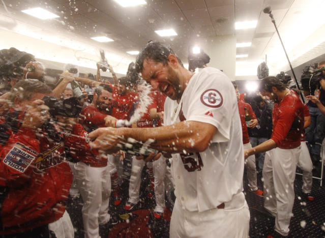St. Louis Cardinals starting pitcher Adam Wainwright celebrates in the clubhouse after Game 5 of the National League Division Series between the St. Louis Cardinals and the Pittsburgh Pirates on Wednesday, Oct. 9, 2013, at Busch Stadium in St. Louis. (AP Photo/post-dispatch.com, Chris Lee)