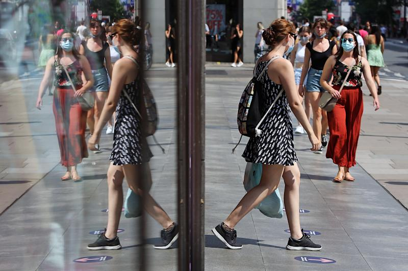 A general view of a busy Oxford Street, London, in the reflection of a shop window, as a girl walks out of a shop wearing a protective face mask due to coronavirus.