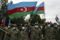 Azerbaijani soldiers wave national flags as they celebrate the transfer of the Lachin region to Azerbaijan's control, as part of a peace deal that required Armenian forces to cede the Azerbaijani territories they held outside Nagorno-Karabakh, in Aghjabadi, Azerbaijan, Tuesday, Dec. 1, 2020. Azerbaijan has completed the return of territory ceded by Armenia under a Russia-brokered peace deal that ended six weeks of fierce fighting over Nagorno-Karabakh. Azerbaijani President Ilham Aliyev hailed the restoration of control over the Lachin region and other territories as a historic achievement. (AP Photo/Emrah Gurel