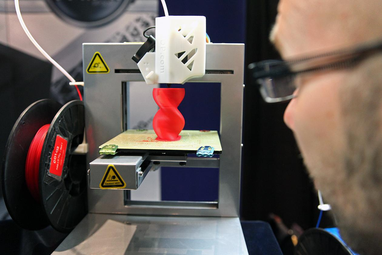"An expo attendee watches demonstration of a 3D desktop printer made by <a target=""_blank"" href=""http://www.pp3dp.com/"">Delta Micro Factory</a>."
