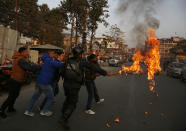 Nepalese students affiliated with Nepal Student Union burn an effigy of Nepalese prime minister Khadga Prasad Oli during a protest in Kathmandu, Nepal, Sunday, Dec. 20, 2020. Nepal's president dissolved Parliament on Sunday after the prime minister recommended the move amid an escalating feud within his Communist Party that is likely to push the Himalayan nation into a political crisis. Parliamentary elections will be held on April 30 and May 10, according to a statement from President Bidya Devi Bhandari's office. (AP Photo/Niranjan Shrestha)