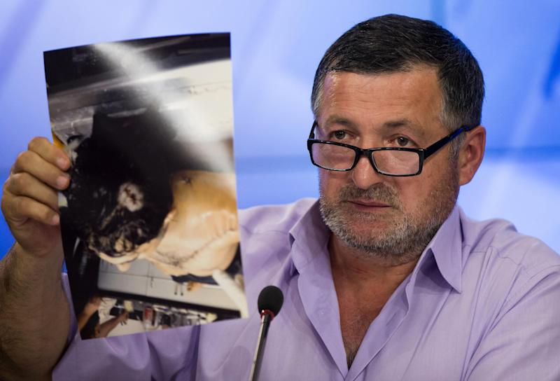 "Abdul-Baki Todashev holds a photo he claims is of his dead son Ibragim Todashev during a news conference in Moscow, Russia, Thursday, May 30, 2013. The father of a Chechen immigrant killed in Florida while being interrogated by the FBI about his ties to a Boston Marathon bombings suspect says agents killed his son ""execution style."" Abdul-Baki Todashev showed journalists 16 photographs on Thursday of his son, Ibragim, in the morgue with what he said were six gunshot wounds to his torso and one to the back of the head. He said the pictures were taken by his son's friend Khusen Taramov. (AP Photo/Alexander Zemlianichenko)"