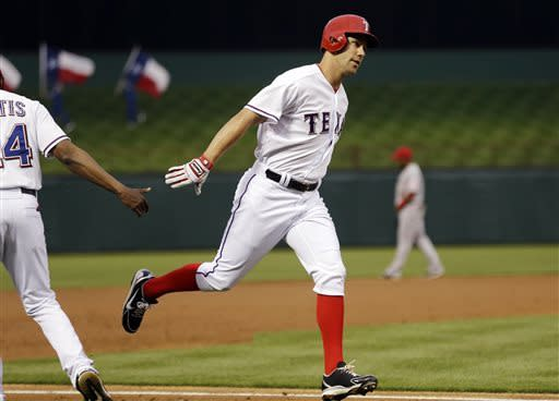 Texas Rangers' David Murphy (7) is congratulated by third base coach Gary Pettis (24) after hitting a home run during the first inning of a baseball game against the Los Angeles Angels, Sunday, April 7, 2013, in Arlington, Texas. (AP Photo/LM Otero)