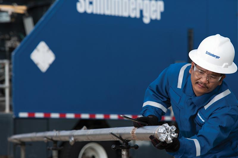 A worker wearing a Schlumberger hard hat pulling a drill bit out of a trailer