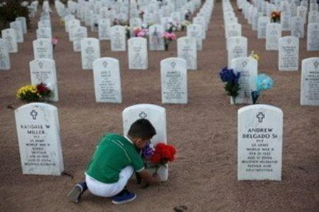 A child places a flower bouquet at the grave of a relative during Veterans Day at Fort Bliss National Cemetery in El Paso, Texas, November 11, 2015. REUTERS/Jose Luis Gonzalez