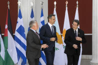 Jordan's King Abdullah II, left, Greece's Prime Minister Kyriakos Mitsotakis, center, and Cyprus' President Nikos Anastasiades make their way for a meeting in Athens, on Wednesday, July 28, 2021. Greece is hosting a one-day trilateral meeting of the three leaders. (AP Photo/Yorgos Karahalis)