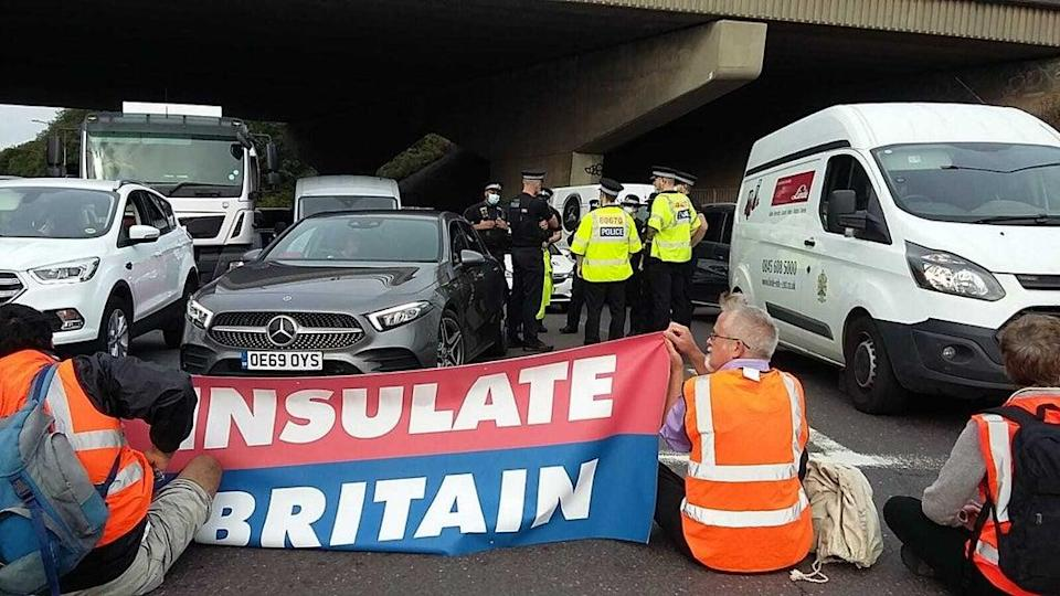 Police speaking to one another as protesters block an M25 junction on Monday (Insulate Britain/PA) (PA Media)