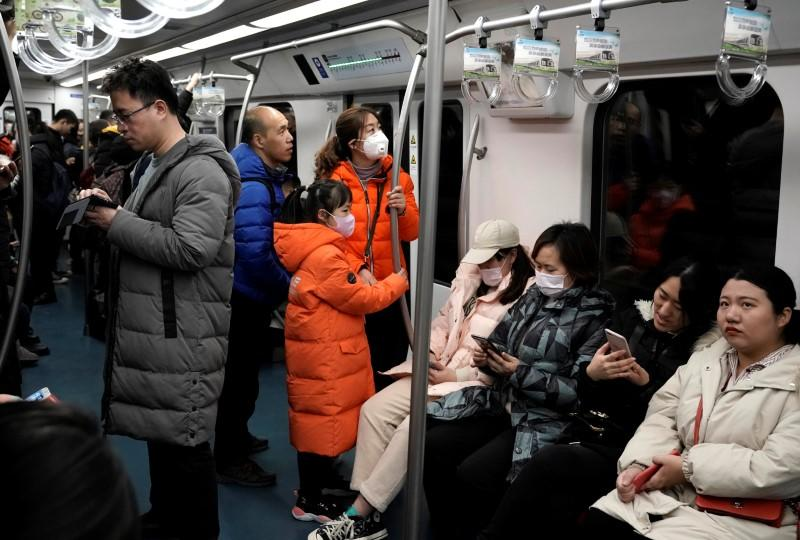 People wearing masks are pictured on the subway in Beijing
