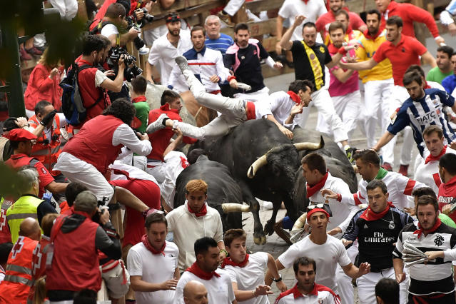 <p>Revellers run as others fall on Miura's fighting bulls during the running of the bulls at the San Fermin Festival, in Pamplona, northern Spain, July 14, 2017. (Photo: Alvaro Barrientos/AP) </p>