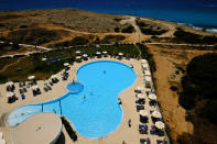 People enjoy their vacations at the pool of Nissi Blue hotel in southeast resort of Ayia Napa, in the eastern Mediterranean island of Cyprus, Saturday, May 22, 2021. Cypriot hotel and other tourism-related business owners say they'd like to see the COVID-19 pandemic-induced uncertainty over travel bookings to the tourism-reliant island nation winding down by July when they're hoping authorities in Cyprus' main markets including the U.K., Russia, Germany and the Scandinavian countries will make it easier for their citizens to travel abroad. (AP Photo/Petros Karadjias)