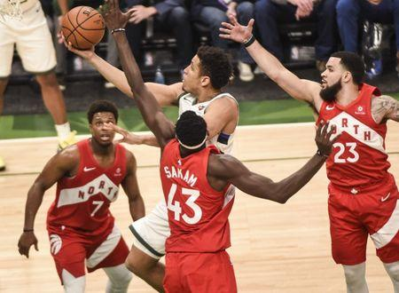 May 23, 2019; Milwaukee, WI, USA; Milwaukee Bucks guard Malcolm Brogdon (13) shoots the ball past Toronto Raptors guard Kyle Lowry (7), forward Pascal Siakam (43) and guard Fred VanVleet (23) in the third quarter in game five of the Eastern conference finals of the 2019 NBA Playoffs at Fiserv Forum. Mandatory Credit: Benny Sieu-USA TODAY Sports