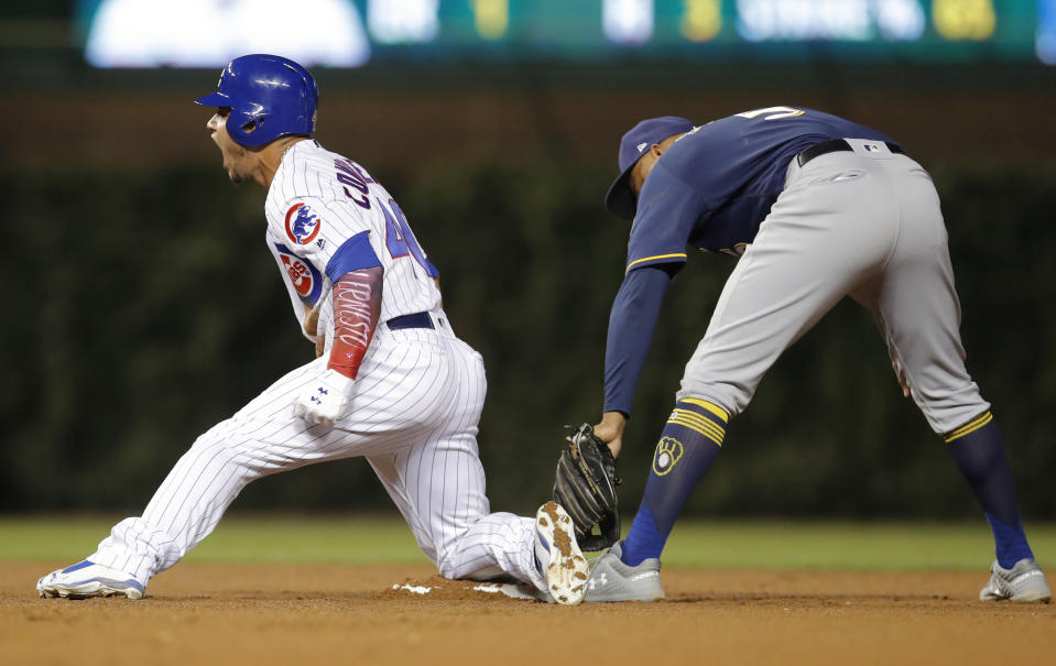 Chicago Cubs' Willson Contreras, left, reacts after sliding into second base safely with a double ahead of a tag from Milwaukee Brewers' Jonathan Schoop during the fifth inning of a baseball game Monday, Sept. 10, 2018, in Chicago. (AP Photo/Jim Young)