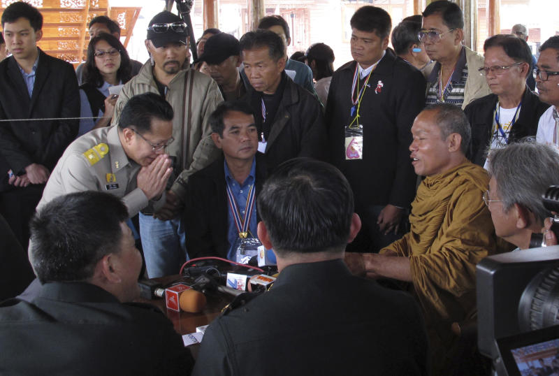 In this photo taken Monday, Jan. 27, 2014, local monk protest leader Luang Pu Buddha Issara, right, is greeted high level police officers asking him to leave the neighboring government building to Bangkok, Thailand. Some government officials have resorted to pleading with protests occupying their government offices where daily functions such as passport controls and immigration issues are backing up. It was an extraordinarily humbling moment for Prime Minister Yingluck Shinawatra's embattled administration, which ascended to power following a landslide election two and a half years ago. (AP Photo/Thanyarat Doksone)