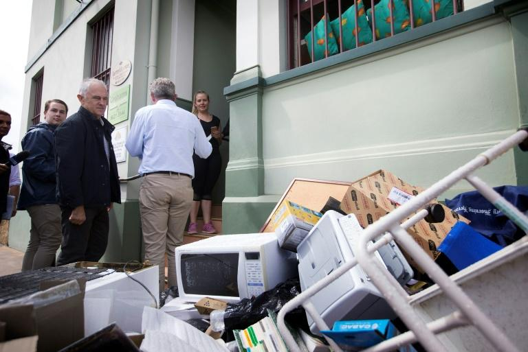 "Prime Minister Malcolm Turnbull (L) said the ""thoughts and prayers of all Australians"" were with those affected, with hundreds of homes and businesses either uninhabitable or destroyed"