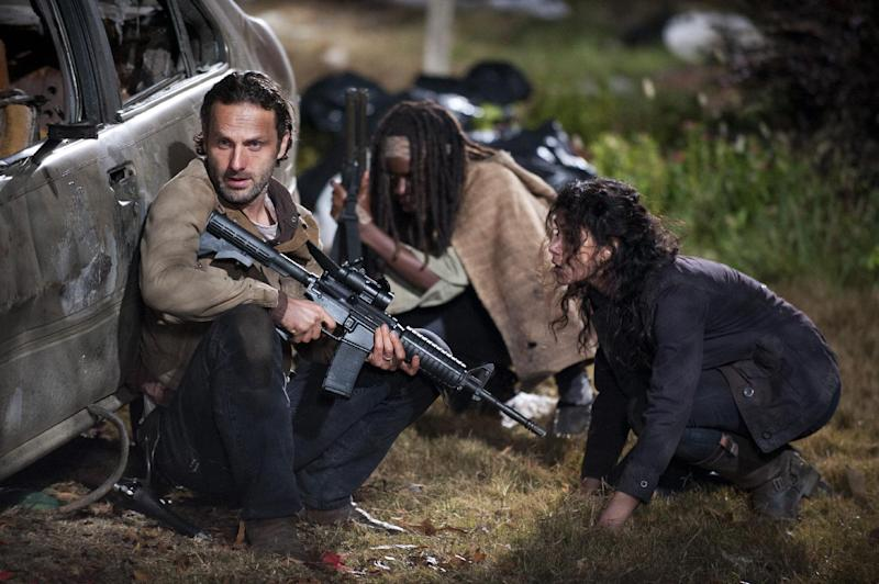 """This publicity photo released by AMC shows, from left, Andrew Lincoln as Rick Grimes, Danai Gurira as Michonne and Melissa Ponzio as Karen, in a scene from Episode 16, """"Welcome to the Tombs"""" from Season 3 of """"The Walking Dead."""" (AP Photo/AMC, Gene Page)"""