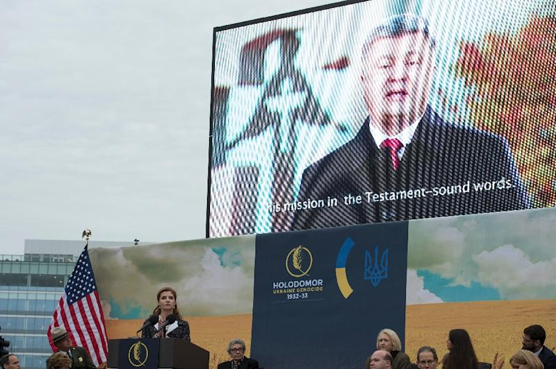 Maryna Poroshenko, First Lady of Ukraine, listens while Ukrainian President Petro Poroshenko is projected on a screen during the unveiling and dedication of the Holodomor Memorial on November 7, 2015 in Washington, DC (AFP Photo/Molly Riley)