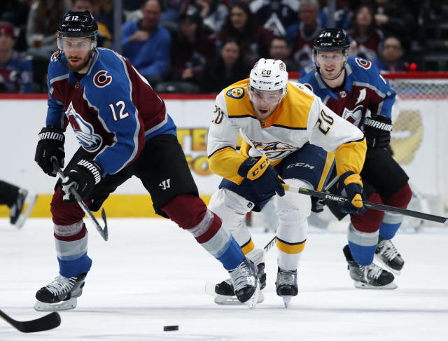 Colorado Avalanche defenseman Patrik Nemeth, front, reaches out for a loose puck in front of Nashville Predators right wing Miikka Salomaki, center, and left wing Blake Comeau during the first period of an NHL hockey game Friday, March 16, 2018, in Denver. (AP Photo/David Zalubowski)