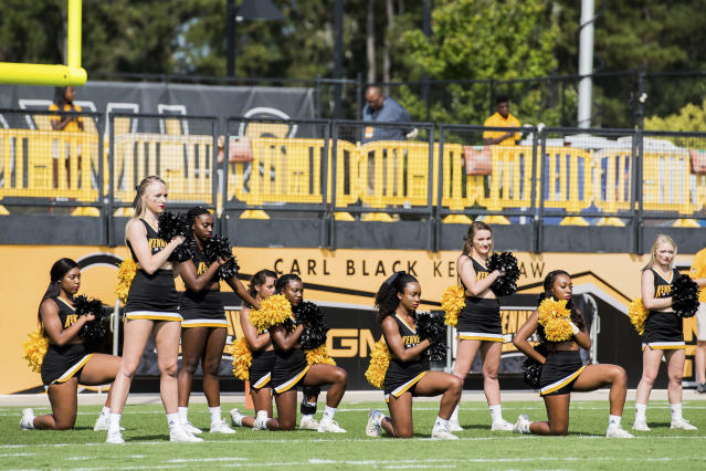 Five Kennesaw State University cheerleaders take a knee during the national anthem prior to a college football game on Sept. 30. (Atlanta Journal-Constitution via AP)