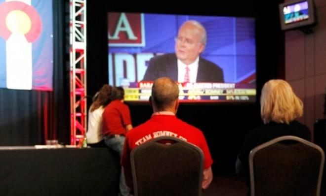 A couple watches Karl Rove on Fox News during a Republican Party election night gathering in Denver, Colo.